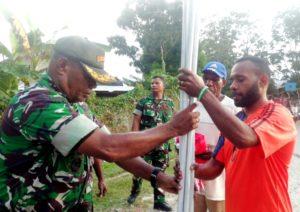 Danrami Sentani. Mayor Infanteri. Jhon F Dahar., menyerahkan tiang bendera kepada salah satu perwakilan pemuda asal pegunungan Erik Brago Tabuni yang berdomisli di Kampung Sereh,(foto, daniel).