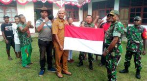 foto bersama Danramil Sentani bersama Kepala Kampung Sereh memegang bendera merah putih disaksikan warga dan anggota koramil,Sentani, (foto, daniel).